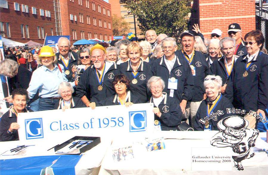 Large group photo of Class of 1958 with Dr. Jane Norman with their Class of 1958 Banner - all are standing together outside during Homecoming.