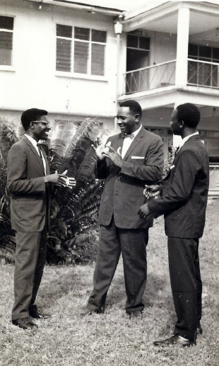Three Black Deaf men conversing with one another standing in front of a white building.