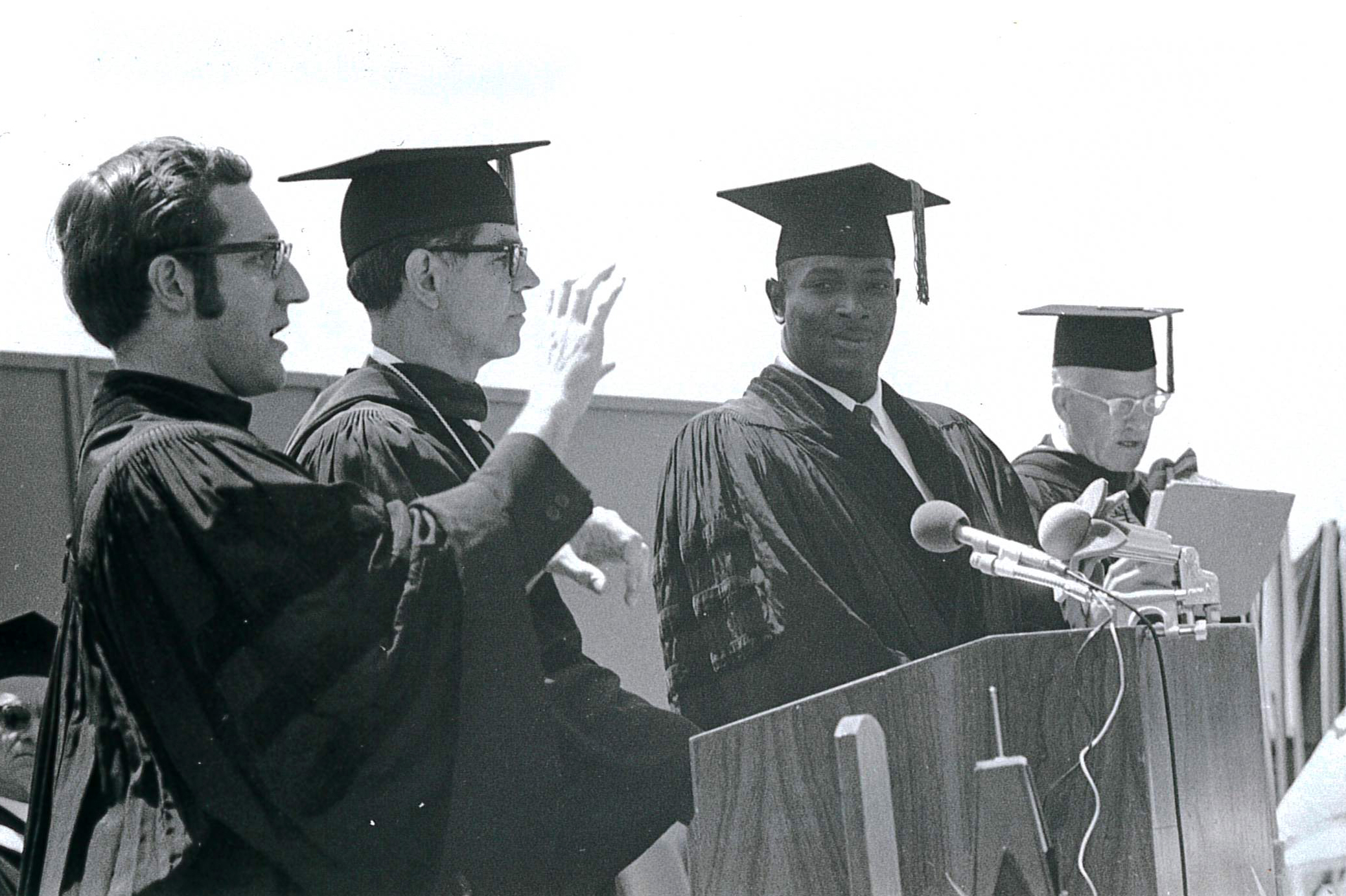 Andrew Foster in Doctoral regalia standing at the podium among three other white men including President Elstad.