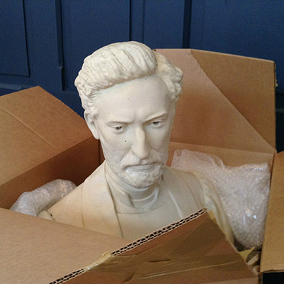 A sculptured bust lies in an opened box.