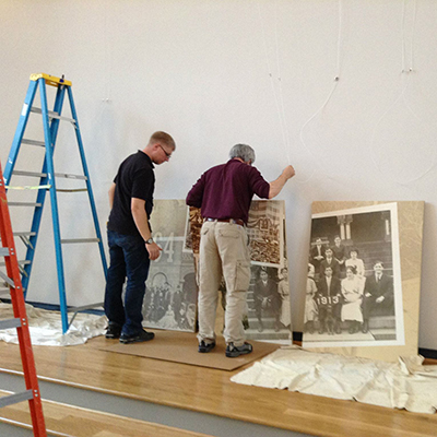 Two men, surrounded by a ladder and some panels in preparations of building a banner for the exhibit.