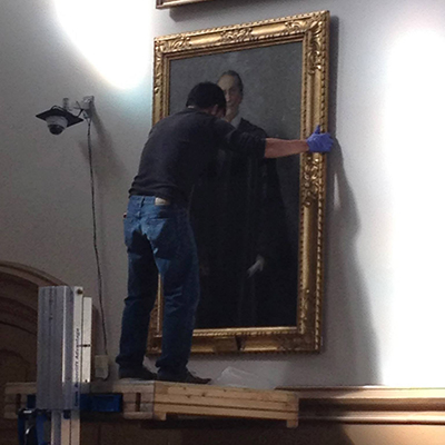 Professional archivist removes a portrait from the wall, carefully.