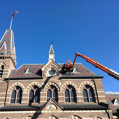 A crane with workers repairing the roof at Chapel Hall