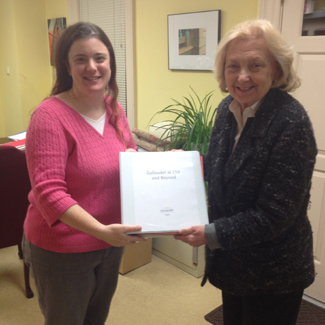 Meredith Peruzzi and Dr. Jane Norman holding a binder of exhibition script that is completed and ready to send to Blair, Inc.
