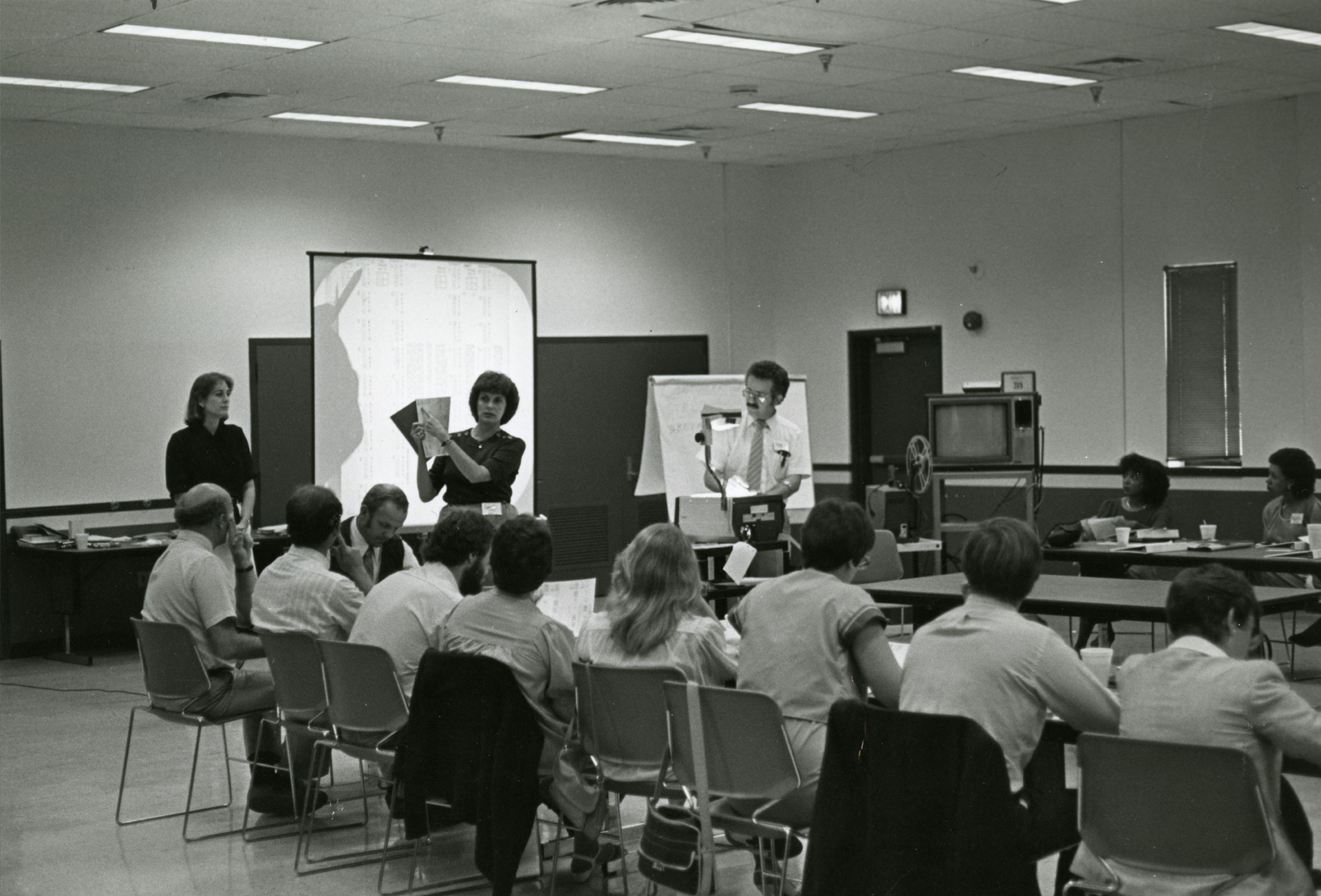 Blk/White photo of classroom looking at students on their desk from behind - not in semi-circle formation.
