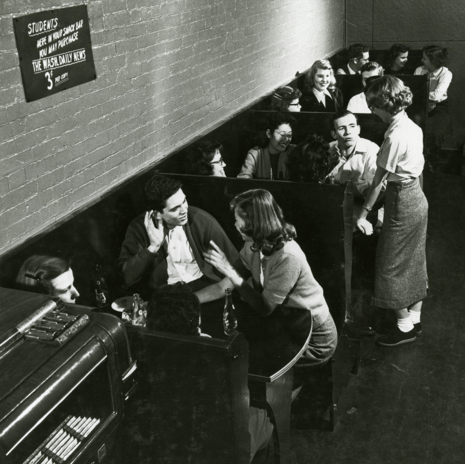Blk/White photo of students sitting in booths.