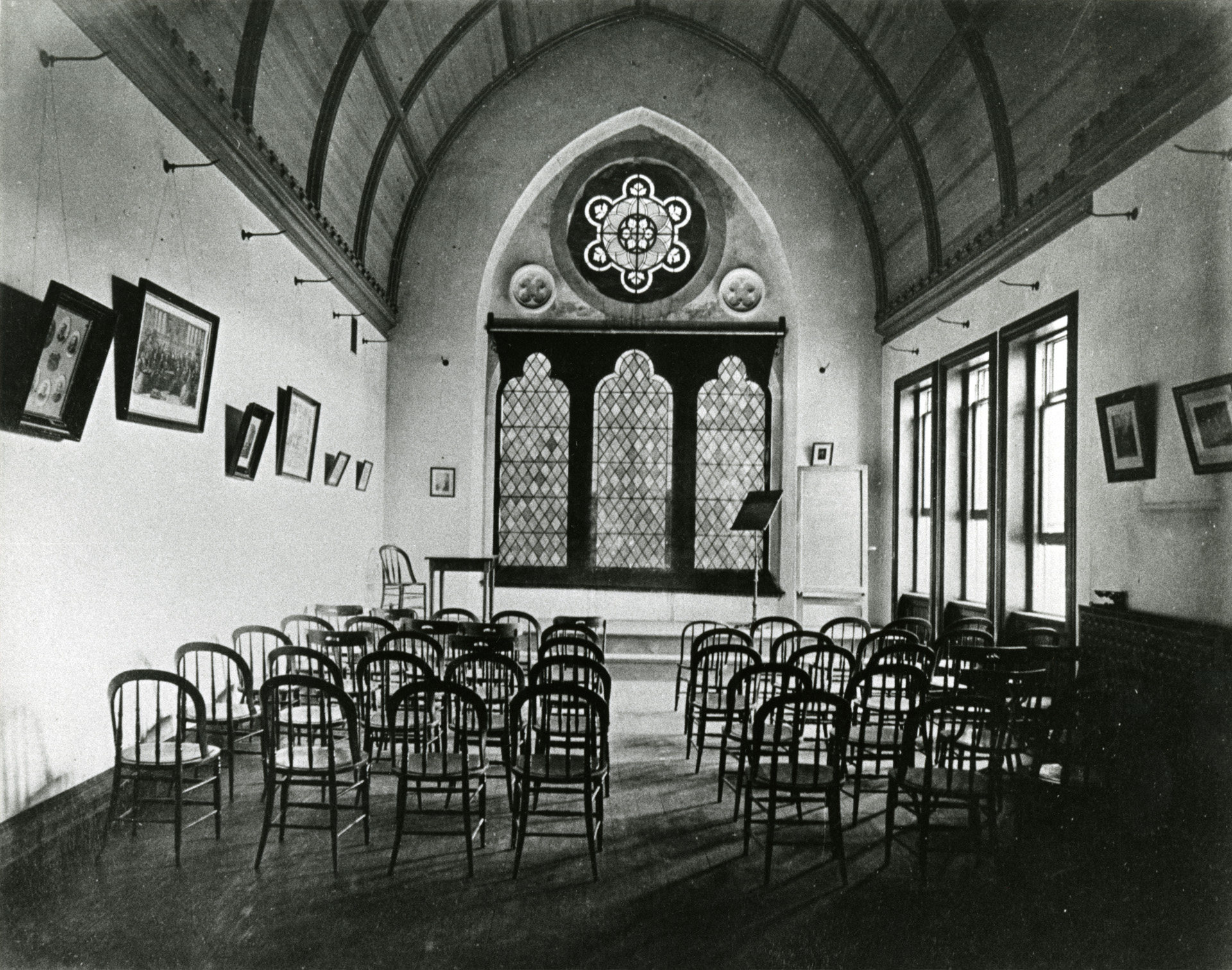 Blk/white photo of an empty Lyceum with chairs. There were frames (of photos, etc.) on the wall. Stained glass in the background.