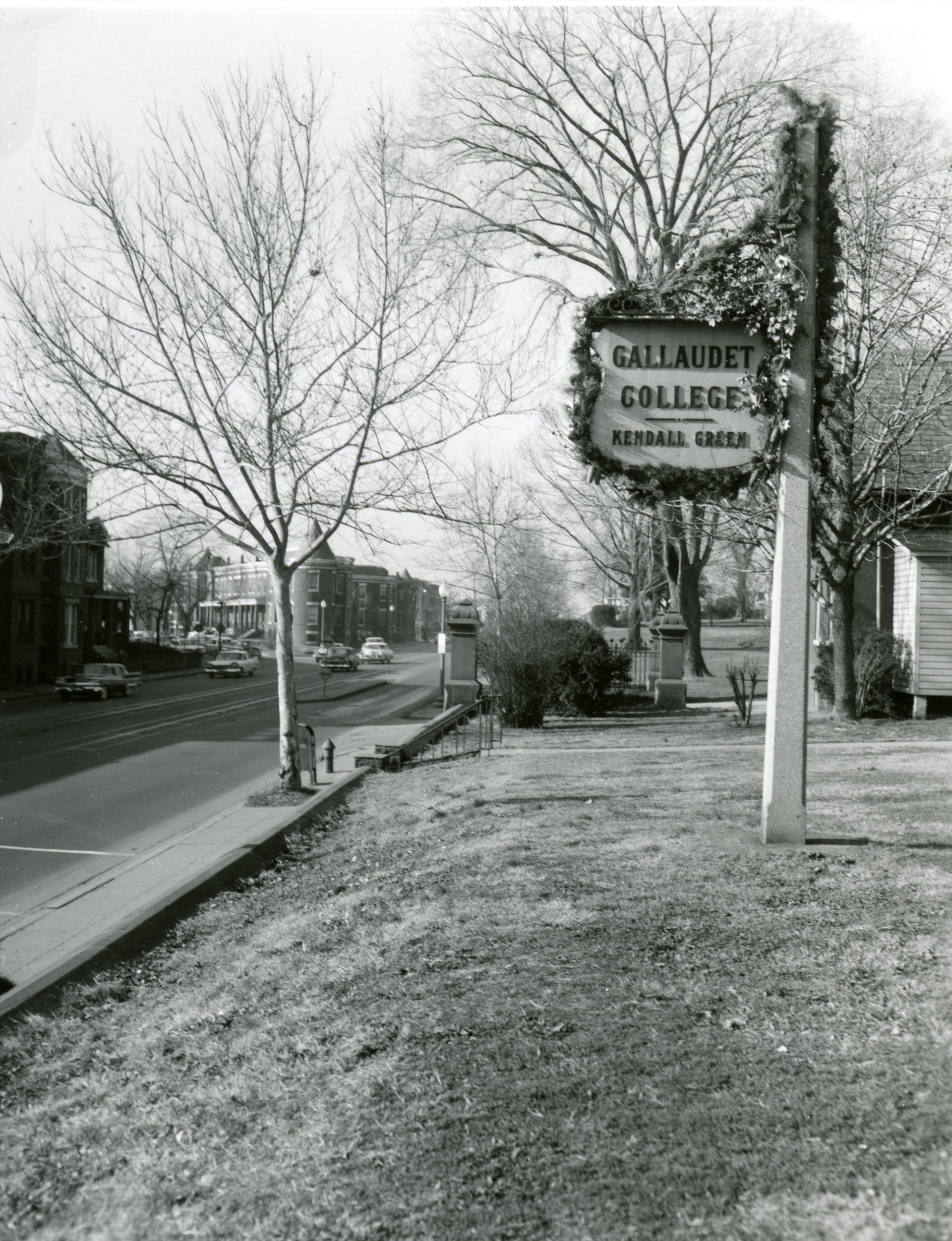 Blk/white photo of old Gallaudet College signage beside Florida Ave, can see the Gate House in the background.