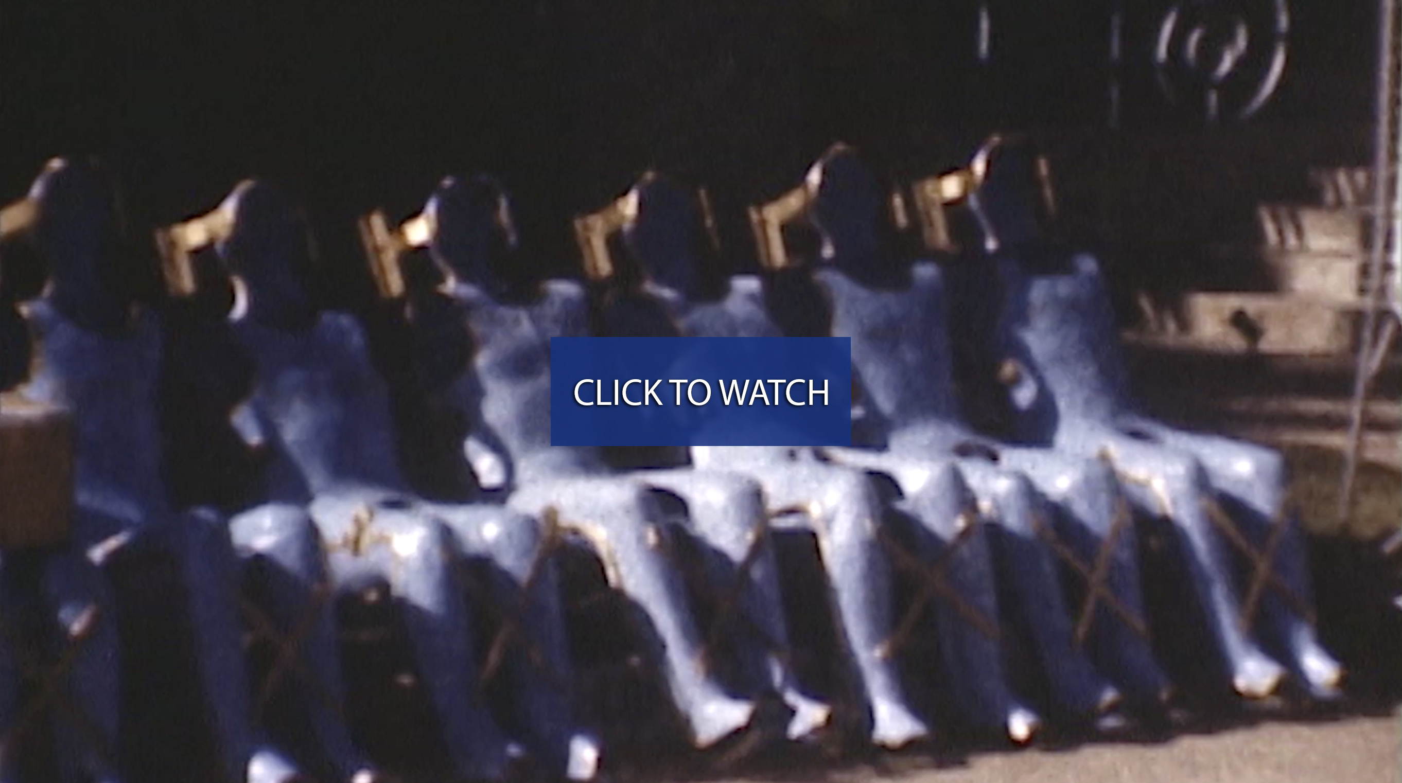 "Rows of body casts in blue tinted video and a button say ""Click here to watch video."""