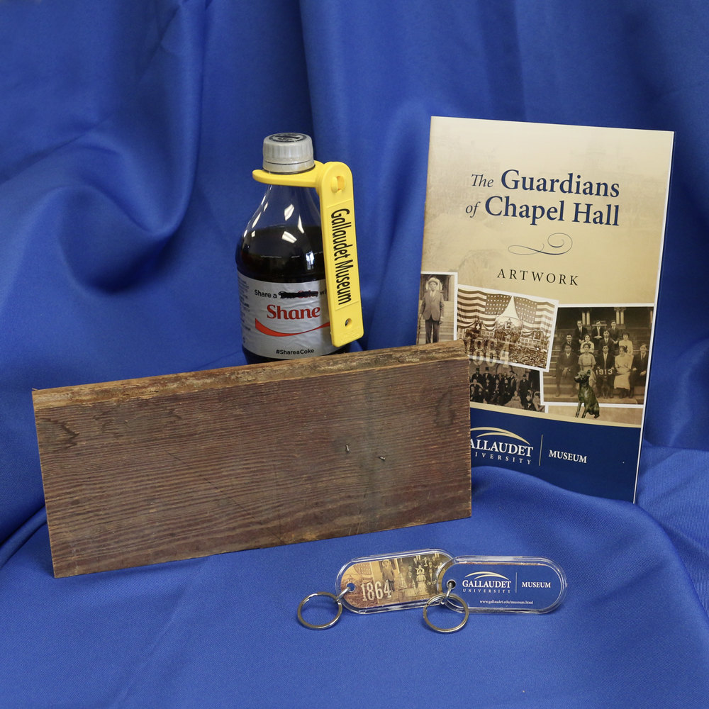 "Museum items for sale - ""Chapel Hall Guardian"" booklet, original piece of wood from Chapel Hall, beverage bottle holder, Gallaudet Museum key chains."