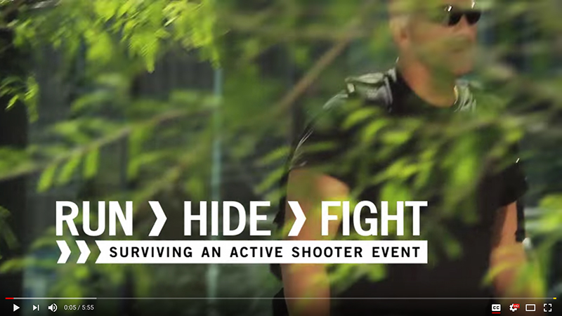 screenshot of the beginning of the video, Run > Hide > Fight. Shows a man walking through trees
