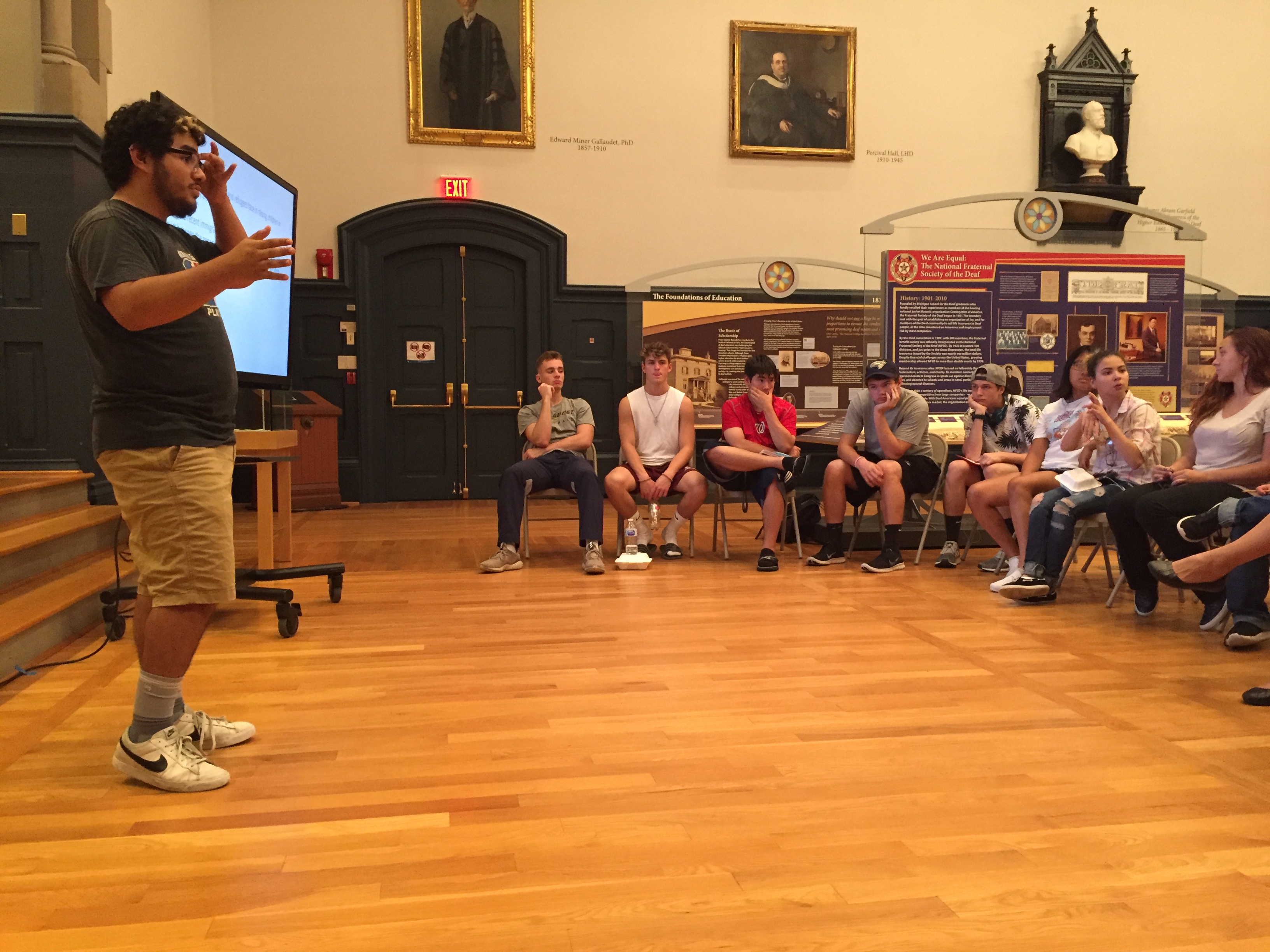 Pablo Gonzalez speaks in front of audience inside of Chapel Hall where the Museum is.