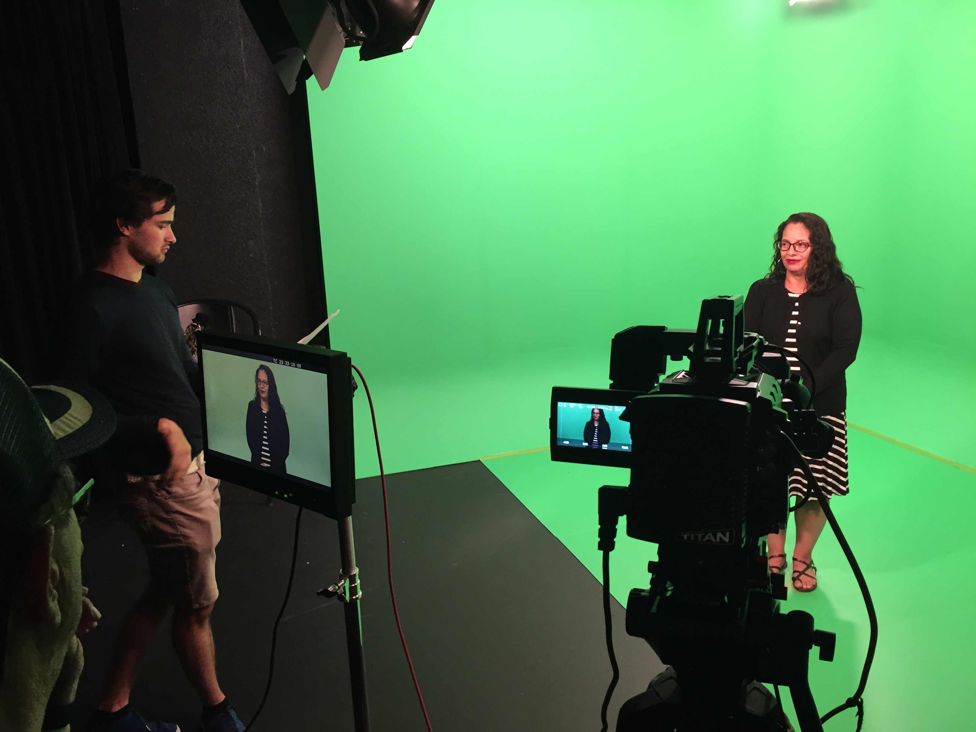 Gideon Firl discussing the film with Norma Moran as she stood inside of green screen area. Cameras and monitors are visible in this photo.